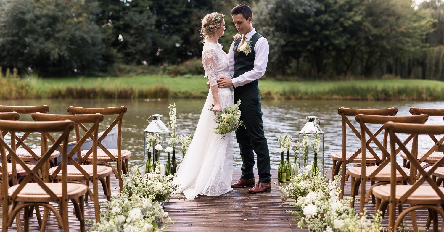 Bride and groom standing on jetty next to lake at Horsley Hale Farm, photo by Sarah Brookes Photography