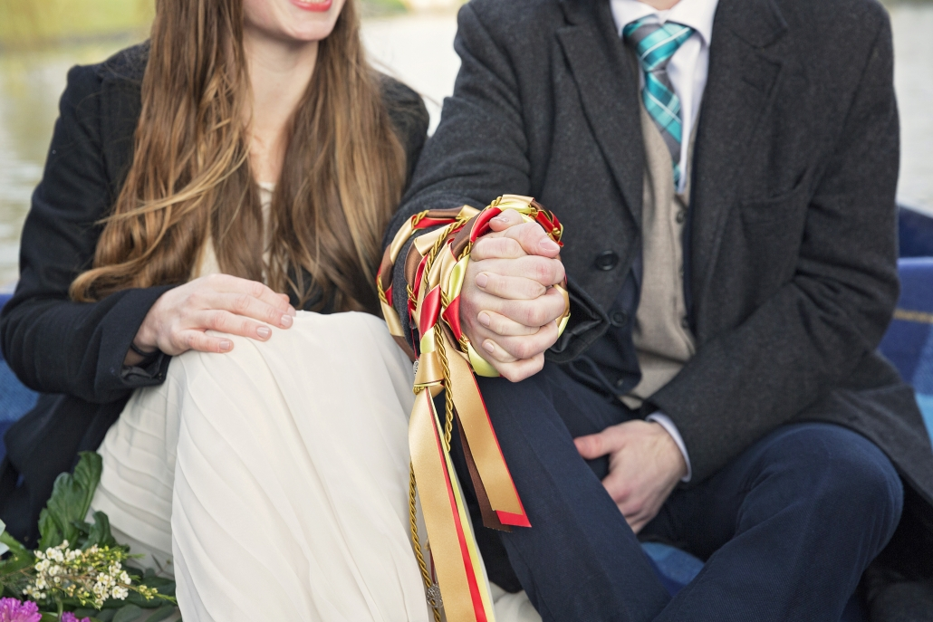 Two hands joined by gold and red ribbons
