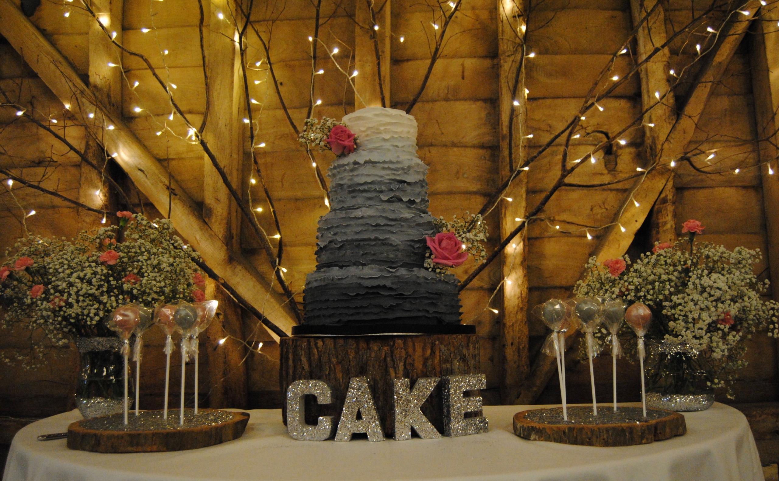A grey and cream wedding cake on a piece of wood