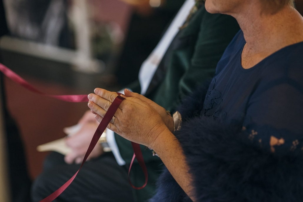Wedding rings are looped on ribbon and held by the bride's mother